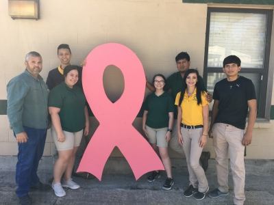 Welding Instructor Randy Jarreau, Javier Maya, Jodie Meche, Jacqueline LaCombe, Victor Torres, Jayln McDonner and Fausto Mejia with the pink yard donated by Rhett Pourciau and an anonymous citizen.